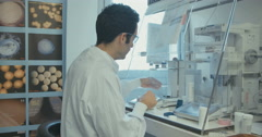 Lab technician weighing pills in a pharmaceutical research lab Stock Footage