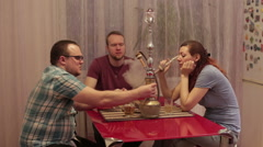 A group of people smoking shisha and playing cards Stock Footage