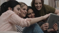 Group of female friends with digital tablet sofa Stock Footage