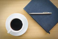 Coffee and notebook on wood table - stock photo