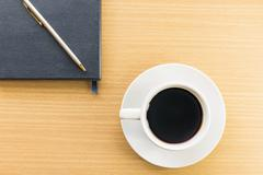 Coffee cup and notebook - stock photo