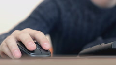 Hand of a man working at computer clicking on mouse typing text on keyboard - stock footage