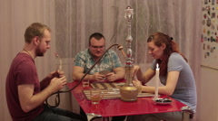 Woman with men smoking shisha and drinking alcohol - stock footage