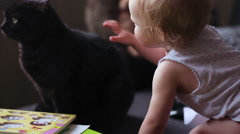 Little baby girl strokes a cat Stock Footage
