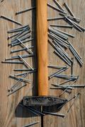 Hammer and batch of nails on wooden planks - stock photo