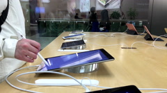 Women playing new ipad pro inside Apple store - stock footage