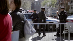 Three NYPD officers hanging out behind police barrier on Lower 5th Ave 4K NYC Stock Footage