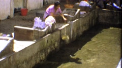 1974: Women washing clothes community activity buckets of dirty water. Stock Footage