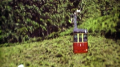 1974: Cable car gondola traveling across dense jungle to scenic lookout. Stock Footage