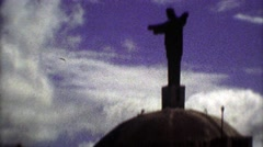 1975: Religious Jesus statue atop mountain silhouette passing clouds. Stock Footage