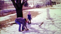 1975: Dad boy throw snowballs at eachother with spring snowstorm. Stock Footage