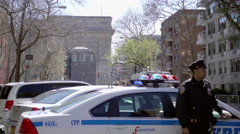 NYPD police officer leaning on car Washington Square Park arch background 4K NYC Stock Footage