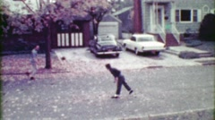 1963: Son and father toss pigskin football around residential roads. Stock Footage