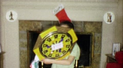 1963: Boy gets dartboard for Christmas gift in front of holiday fireplace. - stock footage