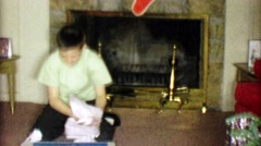 1963: Boy unwraps Electrical Build-It-Set learning Christmas gift. - stock footage