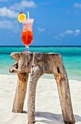Glass of red drink is on the original beach table, Maldives, The Indian Ocean Stock Photos