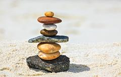 Eight white and brown stones are on sandy beach Stock Photos