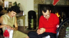 1963: Parents opening holiday Christmas gifts roaring yuletide fireplace. Stock Footage