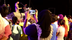 Rock concert Muslim woman using smartphone to video record Stock Footage
