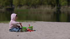 Happy child playing with sand at the beach in summer - stock footage