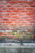 Old red brick wall vertical texture with part of concrete basement beneath - stock photo