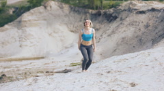 Blonde girl jumping and spinning on the beach Stock Footage
