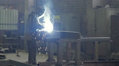Worker welds an i-beam on a factory in a darkness close-up Stock Footage
