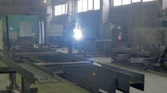 Worker welds an i-beam on a factory in a darkness Stock Footage