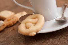 alsatian cookies and cup of coffee on wooden background - stock photo
