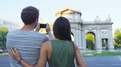Madrid Tourists couple sightseeing talking photo with phone by Puerta de Alaca Stock Footage