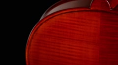 Detail of body of a violin or viola turning at black background Stock Footage