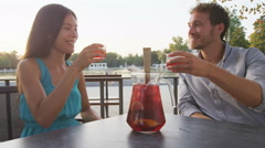 Couple drinking sangria toasting happy having fun sitting at cafe table Stock Footage