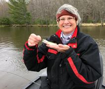 Happy Fisherwoman with a tiny Walleye - stock photo