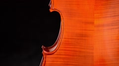 Detail of body of a violin or viola turning at black background - stock footage