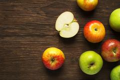 Colorful apples on wooden table. - stock photo