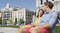 Couple relaxing on bench talking romantic in city park square in Madrid Stock Footage