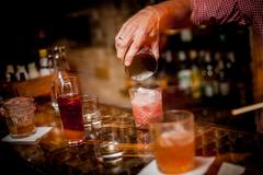 Barman pouring  cocktail into a glass Stock Photos