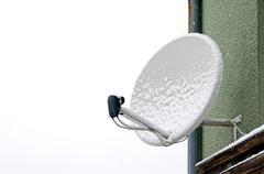 Satellite dish in the winter - stock photo