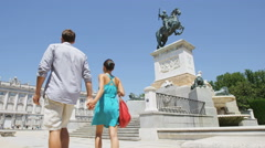 Couple holding hands walking romantic on city park square in Madrid Stock Footage