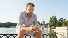 Man sms texting using app on smart phone at sunset in city park Arkistovideo