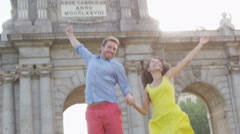 Spain - Madrid Tourists couple jumping cheering by Puerta de Alaca Stock Footage