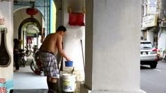 Chinese man cleaning candle shrine Penang - stock footage
