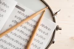 Music score drumsticks and drum tuner over a snare drum Stock Photos