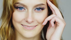 Portrait of a young blue-eyed woman relates her face fingers - stock footage
