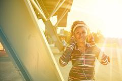 African american fit woman choosing music from an app for running at sunset - stock photo