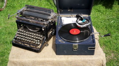 Vintage vinyl record player and old manual typewriter displayed outdoors Stock Footage