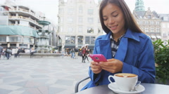 Asian woman texting on phone at outdoor cafe on smart phone drinking coffee Stock Footage