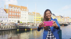 Tourist selfie - Asian woman taking photo on phone at Copenhagen Nyhavn, Denmark Stock Footage