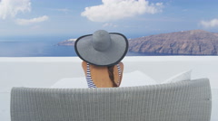 Luxury travel woman relaxing on Santorini vacation looking at famous view Stock Footage