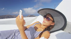 Woman Using Smart phone App Relaxing On Sofa Outdoor -  luxury resort - stock footage